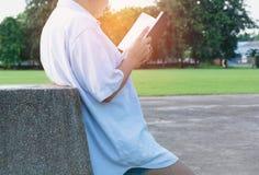 Женщина читая книгу наслаждается руки женщины остатков держа книгу Стоковые Фотографии RF