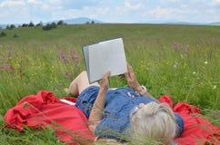 Женщина читая книгу на красном одеяле Стоковое Изображение RF