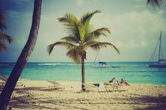 Женщина читая книгу на пляже в Гваделупе стоковые фотографии rf