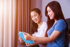 Женщина 2 читая книгу на софе в живущей комнате дома Стоковые Изображения RF