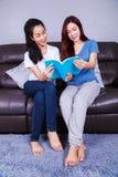 Женщина 2 читая книгу на софе в живущей комнате дома Стоковые Фотографии RF