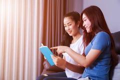 Женщина 2 читая книгу на софе в живущей комнате дома Стоковое Фото