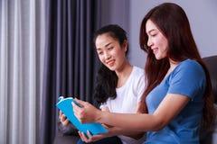 Женщина 2 читая книгу на софе в живущей комнате дома Стоковые Фото