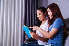 Женщина 2 читая книгу на софе в живущей комнате дома Стоковое Изображение