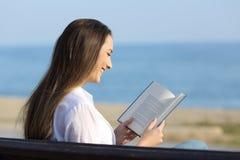 Женщина читая книгу сидя на стенде на пляже Стоковые Изображения RF