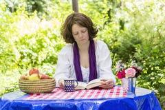 Женщина читая книгу Стоковые Изображения