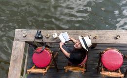 Женщина читая кофе льда лежать и питья книги на стуле в деревянной террасе против красивого вида ослабляет и счастливый день, Стоковая Фотография