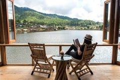 Женщина читая кофе льда лежать и питья книги на стуле в деревянной террасе против красивого вида, ослабляет и счастливый день Стоковое Фото