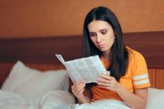 Женщина читая листовку медицины перед принимать таблетки стоковая фотография rf