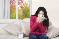 Женщина чихая в ткани Стоковое Фото