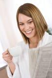 женщина чтения газеты питья кофе завтрака Стоковые Изображения