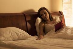 женщина чтения книги кровати Стоковое Изображение RF