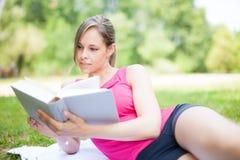 женщина чтения парка книги стоковая фотография