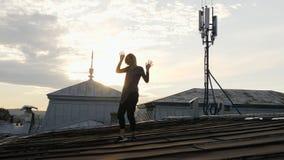 Женщина чувствуя счастливый пока слушая музыка в наушниках, танцуя на крыше Стоковые Фото