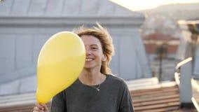Женщина чувствуя счастливый пока слушая музыка в наушниках, танцуя на крыше Стоковое Фото