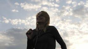 Женщина чувствуя счастливый пока слушая музыка в наушниках, танцуя на крыше Стоковое Изображение
