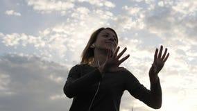 Женщина чувствуя счастливый пока слушая музыка в наушниках, танцуя на крыше Стоковая Фотография