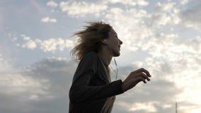 Женщина чувствуя счастливый пока слушая музыка в наушниках, танцуя на крыше Стоковые Изображения