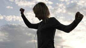 Женщина чувствуя счастливый пока слушая музыка в наушниках, танцуя на крыше Стоковое фото RF