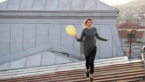 Женщина чувствуя счастливый пока слушая музыка в наушниках, танцуя на крыше Стоковые Фотографии RF