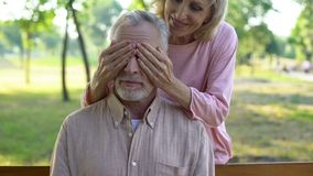 Женщина шаловливо закрывая супруга наблюдает, встречающ outdoors, счастье в старости стоковые фотографии rf