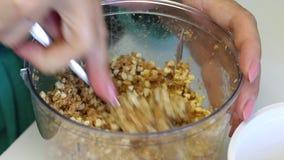 Женщина шаркает завалка для конфеты Задавленные арахисы в шаре blender Для делать popcakes сток-видео