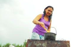 Женщина шевелит суп с деревянной ложкой в чайнике на огне Конец-вверх видеоматериал