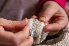 Женщина шить кнопку с потоком и иглой стоковые фотографии rf