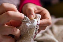 Женщина шить кнопку с потоком и иглой стоковые изображения