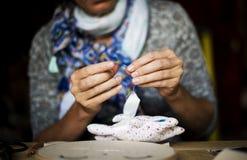 Женщина шить handmade куклу на таблице стоковая фотография rf