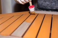 Женщина штрихует деревянный стол с свежей краской Стоковые Изображения