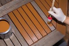 Женщина штрихует деревянный стол с свежей краской Стоковая Фотография RF