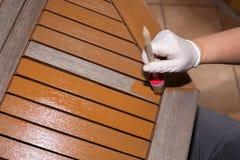 Женщина штрихует деревянный стол с свежей краской Стоковое Фото