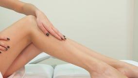 Женщина штрихует ее ногу на таблице массажа стоковые фотографии rf