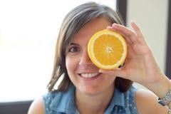 Женщина шутя с апельсином Стоковое фото RF