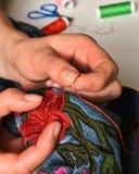Женщина шьет с иглой и красным потоком и на заднем плане некоторый швейный набор стоковые фото