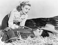 Женщина щекоча ее спать парня с частью соломы (все показанные люди более длинные живущие и никакое имущество не существует sup стоковые изображения