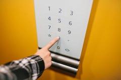 Женщина щелкает дальше электронную кнопку в современном лифте Внутри лифта Стоковые Изображения