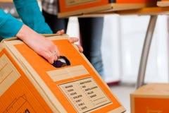 Женщина 2 с moving коробкой в ее доме стоковые изображения