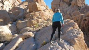 Женщина Active зрелая идя и взбираясь вверх скалистый цвет Sandy камней акции видеоматериалы