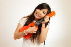 Женщина Aian наслаждается ее гавайской гитарой Стоковая Фотография RF