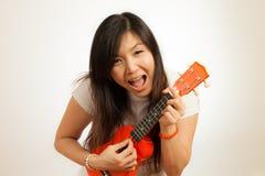 Женщина Aian наслаждается ее гавайской гитарой Стоковое фото RF