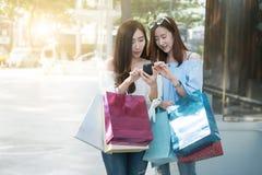 Женщина aisin 2 детенышей используя ее smartphone и хозяйственную сумку владением Стоковые Изображения