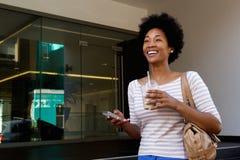 Женщина Bappy держа мобильный телефон и кофе снаружи стоковые фото