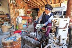 Женщина Bayi делая серебряный бак Heqing известно для продукции artigianal серебряных инструментов Стоковая Фотография RF