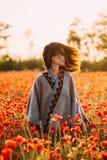 Женщина Boho стильная идя в красный луг маков стоковые изображения rf
