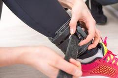 Женщина buckling кожаный ремень поддержки к лодыжке стоковая фотография rf