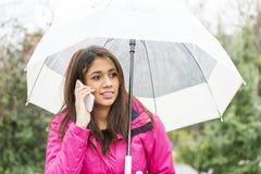 Женщина Cheerfull с зонтиком говоря мобильным телефоном стоковые фотографии rf