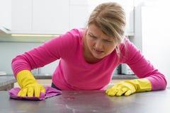 Женщина clening пятно на счетчике кухни стоковые фотографии rf