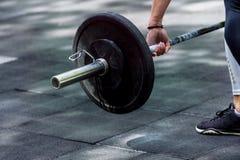 Женщина Crossfit подготавливая для ее разминки поднятия тяжестей с тяжелой гантелью стоковое изображение rf
